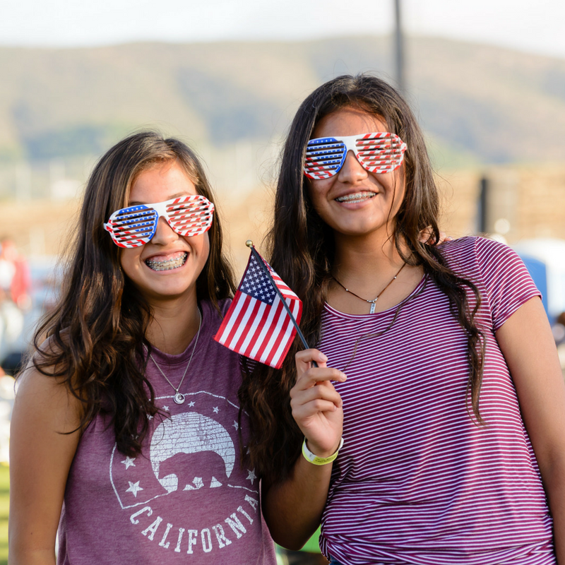 Two girls waving American flags for Fourth of July