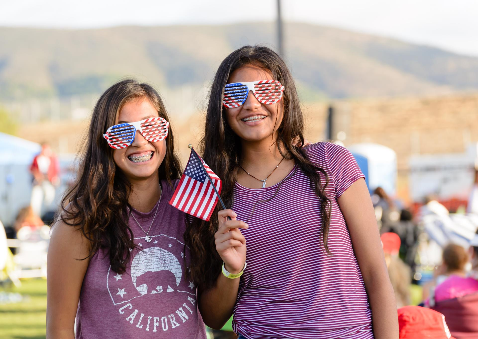 Two girls holding small American flag during Fourth of July event